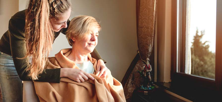 Personlig assistent hjälper kvinna med filt